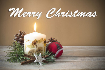 "Christmas decoration with candle, pine, bauble, with text in English ""Merry Christmas"" in wooden background"