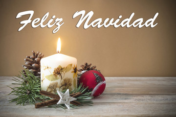 "Christmas decoration with candle, pine, bauble, with text in Spanish ""Feliz Navidad"" in wooden background"