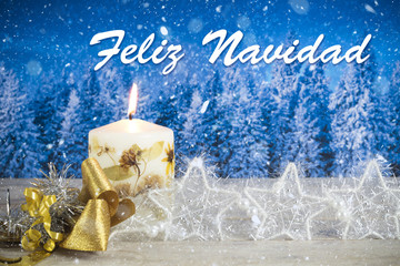 "Christmas decoration with candle, golden bow, silver stars, with text in Spanish ""Feliz Navidad"" in a blue forest background"