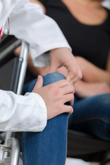 male orthopedic doctor examining womans knee in clinic