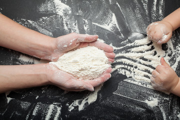 Mom's hands hold a handful of flour and pass it to the child.