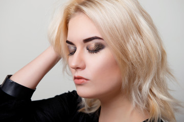 Blonde woman with bright makeup on the eyes closed and the hand in her hair on white isolate closeup