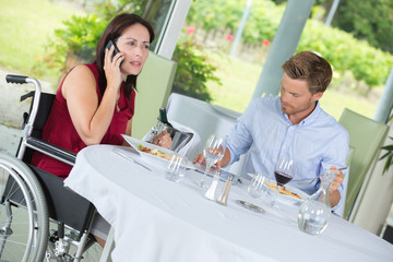 woman in wheelchair using phones in restaurant