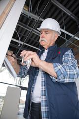 senior electrician wiring a wall socket