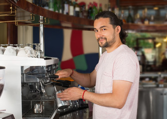 Handsome young smiling male barista preparing coffee drink using coffee machine.