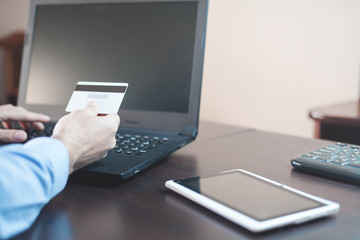 Man holding credit card and using laptop. Online payment and shopping