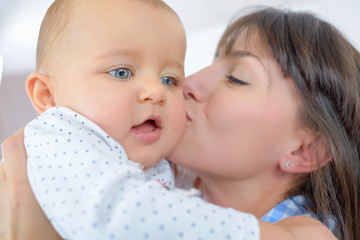 closeup of mother kissing baby