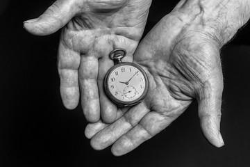 Time concept. Vintage clock in old senior wrinkled male hands on black background