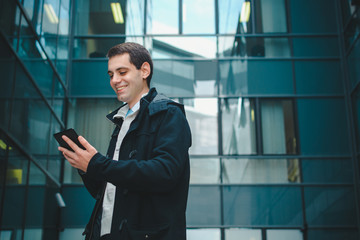 Young businessman using tablet in front of office