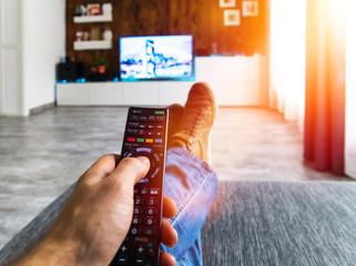 Zappen / Fernsehen auf der Couch mit Fernbedienung in der Hand