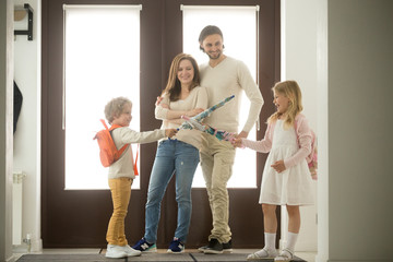 Sister and brother play umbrellas, kids boy and girl having fun standing at hallway, happy family of four spending time together, children fighting get ready to go out with parents, siblings rivalry