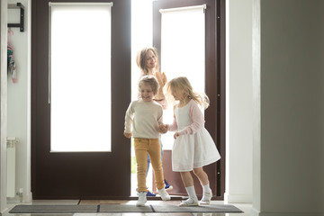 Happy young mother with son and daughter opening door coming back home from mall, single mom and small kids returning to house holding paper bag with food, family grocery shopping together concept