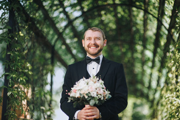 The happy groom is holding a wedding bouquet and sincerely smiling. Groom in a black suit on the nature background.