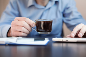 Man drink coffee and using tablet.