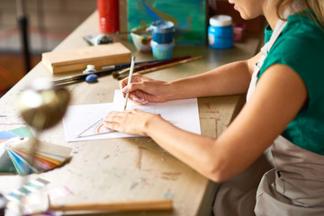 Closeup of unrecognizable young woman drafting sketch with pencil for art and craft project sitting at wooden table in workshop