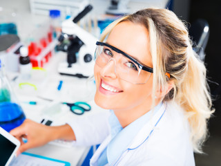 Young attractive woman scientist writing research report in the laboratory