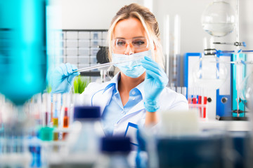 Young attractive female scientist preparing laboratory equipment for tests