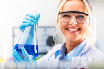 Young attractive female scientist holding a flask with blue liquid substance in the laboratory