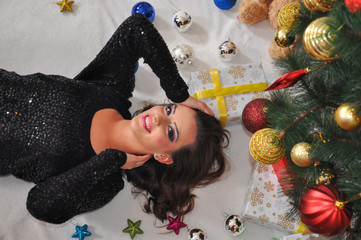 Beautiful young woman lies under a Christmas tree. Woman waiting a New Year