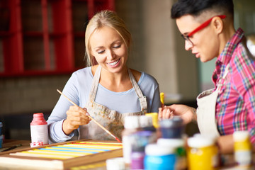 Portrait of two modern female artists enjoying  working together in art studio painting pictures, focus on pretty blonde woman smiling happily