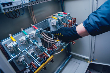 Electricians hands testing switches in electric box. Electrical panel with fuses and contactors