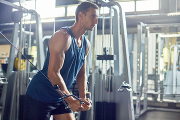 Side view portrait of handsome muscular man using exercising machines in modern gym, copy space
