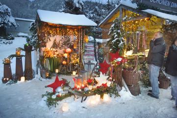 Weihnachtsmarkt in Bayern mit romantischen Holzbuden im Schnee