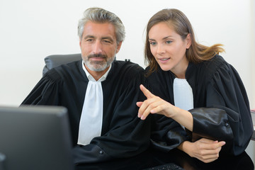 lawyers looking at computer in court gowns