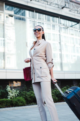 Perfect day to explore new city! Beautiful young woman in sunglasses looking away with smile while pulling her luggage outdoors.