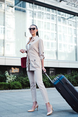 Businesswoman on a trip. Full length of beautiful young woman in sunglasses looking away with smile while pulling her luggage outdoors.