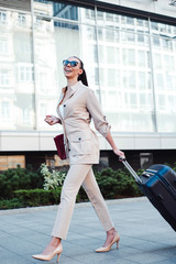 Greeting her vacation with a smile. Full length of beautiful young woman in sunglasses looking away with smile while pulling her luggage outdoors.