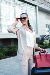 Beautiful young woman adjusting her sunglasses and looking away with smile while pulling her luggage outdoors