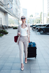 Beauty on the way to her business trip. Full length of beautiful young woman in sunglasses looking at camera with smile while pulling her luggage outdoors on a go.