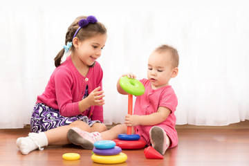 Little Girl And Her Baby Sister Are Playing With Toys Together At Home
