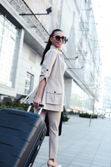 Amazing beauty on her way to airport. Rear view full length of beautiful young woman in sunglasses looking at camera with smile while pulling her luggage outdoors on a go.