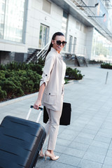 Business lady on her way to airport. Rear view full length of beautiful young woman in sunglasses looking at camera with smile while pulling her luggage outdoors on a go