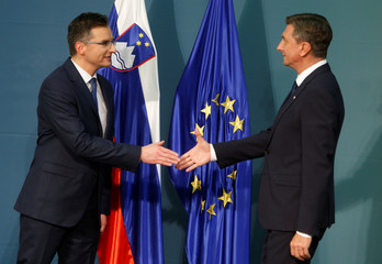 Presidential candidates Borut Pahor and Marjan Sarecreacts shake hands after first results of the second round of the presidential elections in Ljubljana