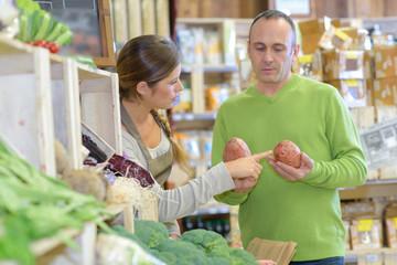 Shop assistant advising customer holding potatoes