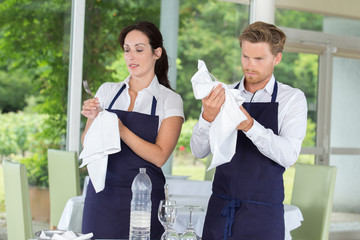 waitress examining a clean wine glass in restaurant