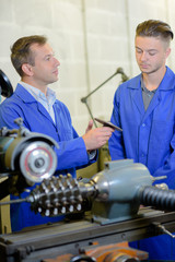 Junior and senior engineers in workshop