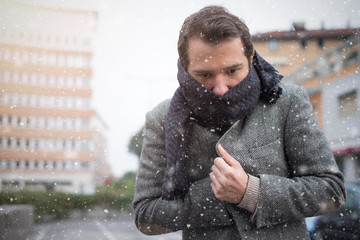 Man casual dressed in the city on a  winter seasonal day and freezing