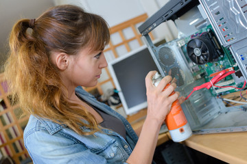 Woman spraying aerosol inside tower computer