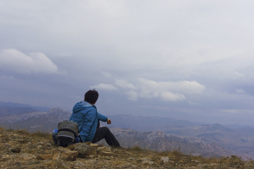 Rear view of a woman sitting at the top of a mountain, looking into the distance on the top of mountain. Background is mountains and cloudy sky.