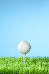 Series of golfing equipment concept pictures..Shot in studio on grass with blue background: Ball on Tee with Copy Space