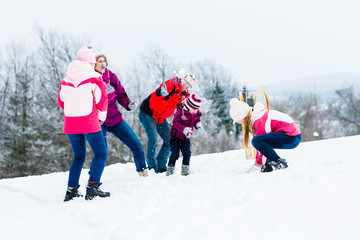Family with kids having snowball fight in winter with fun