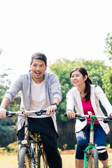 Young Asian couple laughing together while riding bicycles outdoors in summer