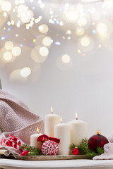 White burning advent candles with christmas decorations and bokeh lights