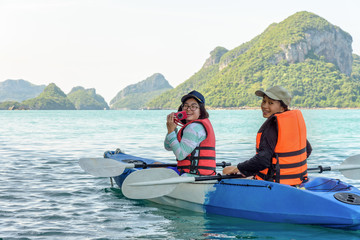 Two women are mother and daughter using a camera take pictures on kayak while travel by boat with happy on the sea at Ko Wua Ta lap islands in Mu Ko Ang Thong National Park, Surat Thani, Thailand