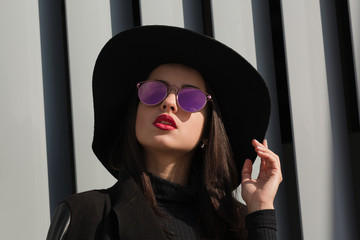 Closeup shot of luxury young woman with bright makeup and shiny hair wears hat and sunglasses
