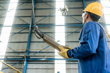 Low-angle view of a skilled Asian worker controlling industrial hook for lifting